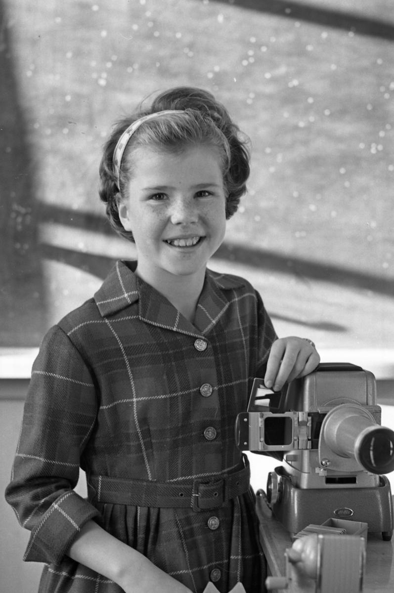 FN-dag i skolan. Karin Ohlsson-Seffer. Flicka som håller en diabild i handen. Hon ska stoppa in den i diaprojektorn. Framför projektorn står asken med diabilder. Där finns också en pennvässare med vev.