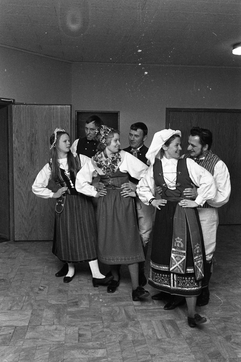 Folkdansare i foajén på Medborgarhuset. Tre par, i folkdräkt, är uppställda.