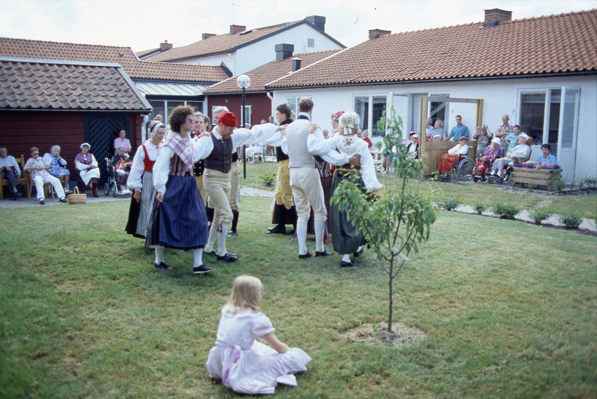 Dansuppvisning, av Arboga Folkdansgille, på äldreboendet Strömsborgs innegård. Dansarna, iklädda folkdräkt, uppträder på gräsmattan. De boende, somliga i rullstol, och deras anhöriga, sitter efter husväggarna och ser på. Det är midsommartid.