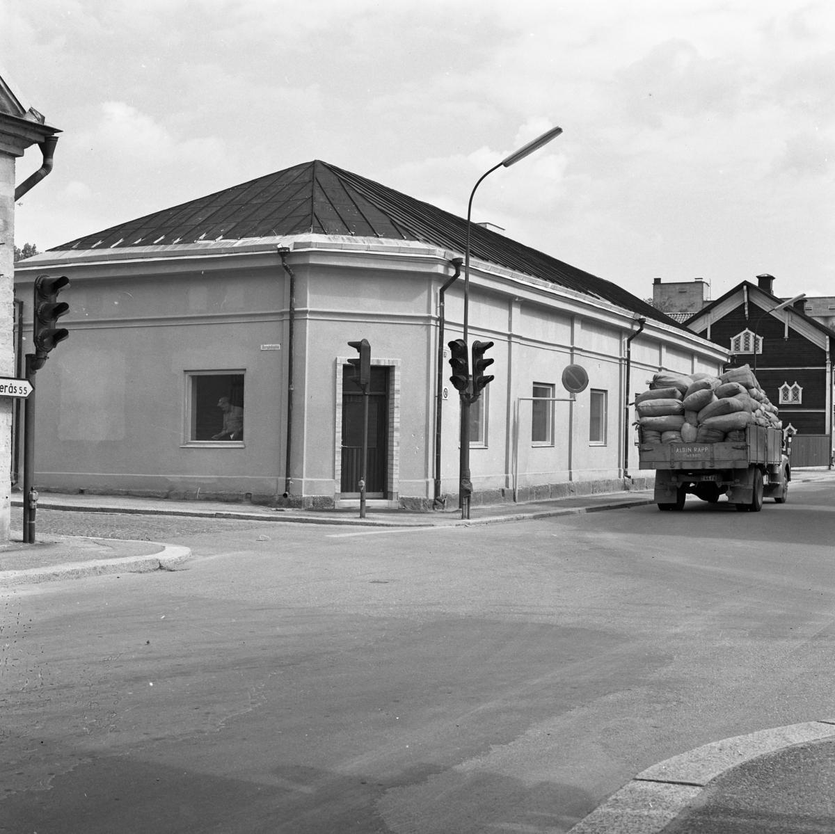 Korsningen Hamngatan - Herrgårdsgatan. Huset renoveras på insidan, en hantverkare syns i fönstret. På Östra Hamngatan kör en lastbil från Albin Rapps Konfektionsfabrik. Den är lastad med säckar.