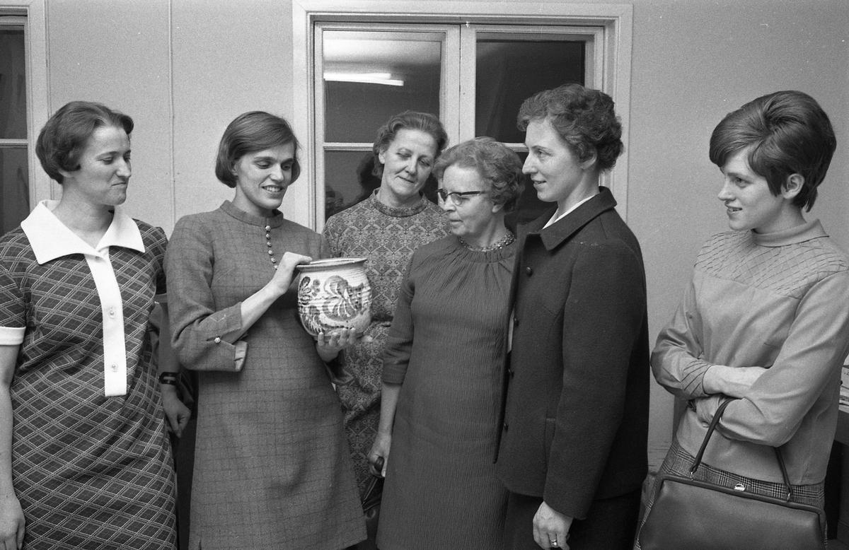 """En grupp kvinnor är på besök i Åhuset, hos keramiker Kerstin Hörnlund. Kerstin visar en kruka hon drejat. Kerstin är gravid och väntar sonen Paul. Läs Kerstins text """"Konstnärsliv i Arboga - möten och minnesbilder"""" i Arboga Minnes årsbok 1998."""