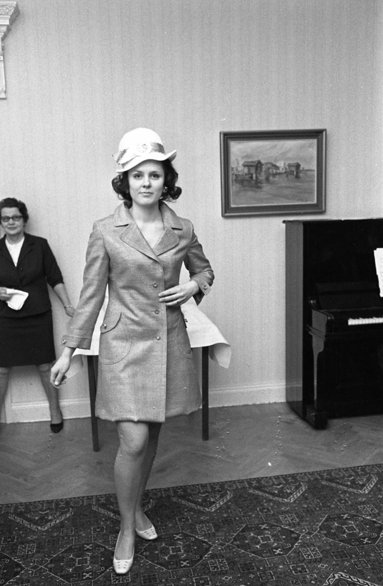 TBV ordnar modevisning. Här kommer mannekängen Lotta Hansson, iklädd hatt och kappa. Till höger skymtar ett piano. Eftersom Sture Melander ses på en bild i sammanhanget, kan man gissa att kläderna kommer från Öhrman & Melander.