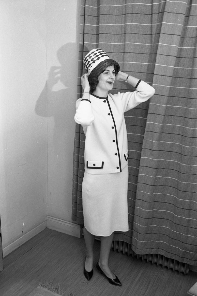 Öhrman och Melander har modevisning. Personalen och kvinnor från Arboga Lottakår mannekängar. Här förbereder sig Marianne Rosenkvist för catwalken. Hon är iklädd en dräkt och hatt. Kvinna i provhytt.