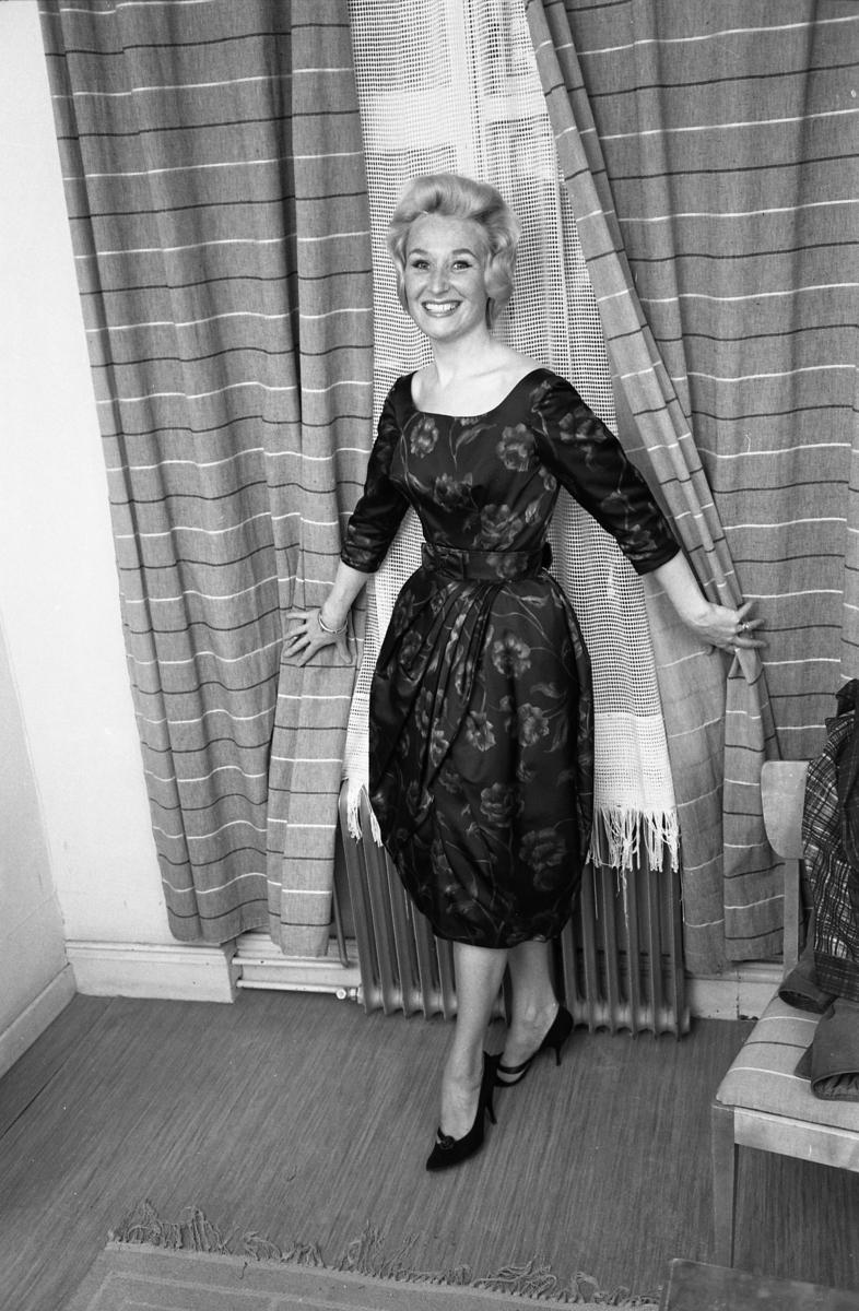 Öhrman och Melander har modevisning på Folkan/Medborgarhuset. Personalen och medlemmar från Arboga Lottakår ställer upp som mannekänger. Här är en kvinna, i klänning, i omklädningsrummet.