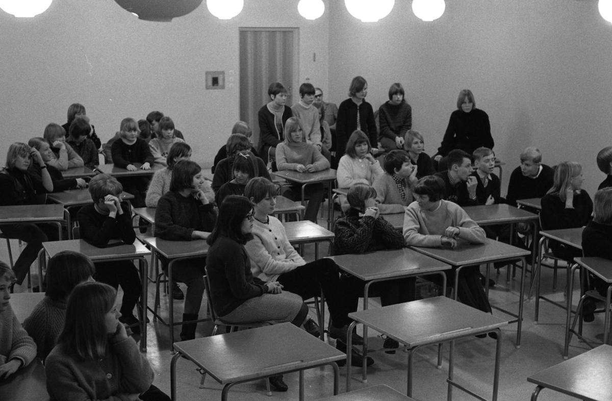 Två årskurser sitter i samma klassrum och lyssnar på musik. Eleverna sitter vid bänkar. Mitt i bild, i ljus kjol, mörk jumper och glasögon sitter Agneta Östman. Vid bänkparet bakom henne sitter Anna-Greta Sjöberg och Käthe Tiborn. I bänken bredvid henne sitter Ove Norman. Längst bak i salen, ovanpå en bänk, sitter Britt-Lis Kempe i mörk jumper med ljus stickning.