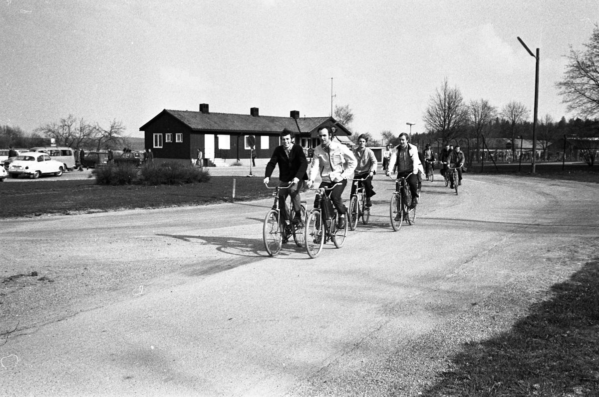 Arbetsdagen är slut och människor cyklar hem från CVA, Centrala Verkstaden Arboga. De två första männen är Sören Wester (till vänster) och Sören Karlsson alternativt Lindström (till höger). I bakgrunden ses bilparkeringen och byggnaden där vakten sitter.