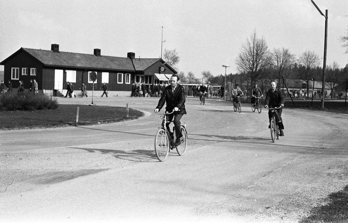 """Män som cyklar hem från arbetet på CVA, Centrala Verkstaden Arboga. I bakgrunden ses grinden och """"vakten"""" (huset där vakten sitter). Människor är på väg till bilparkeringen och busshållplatsen."""