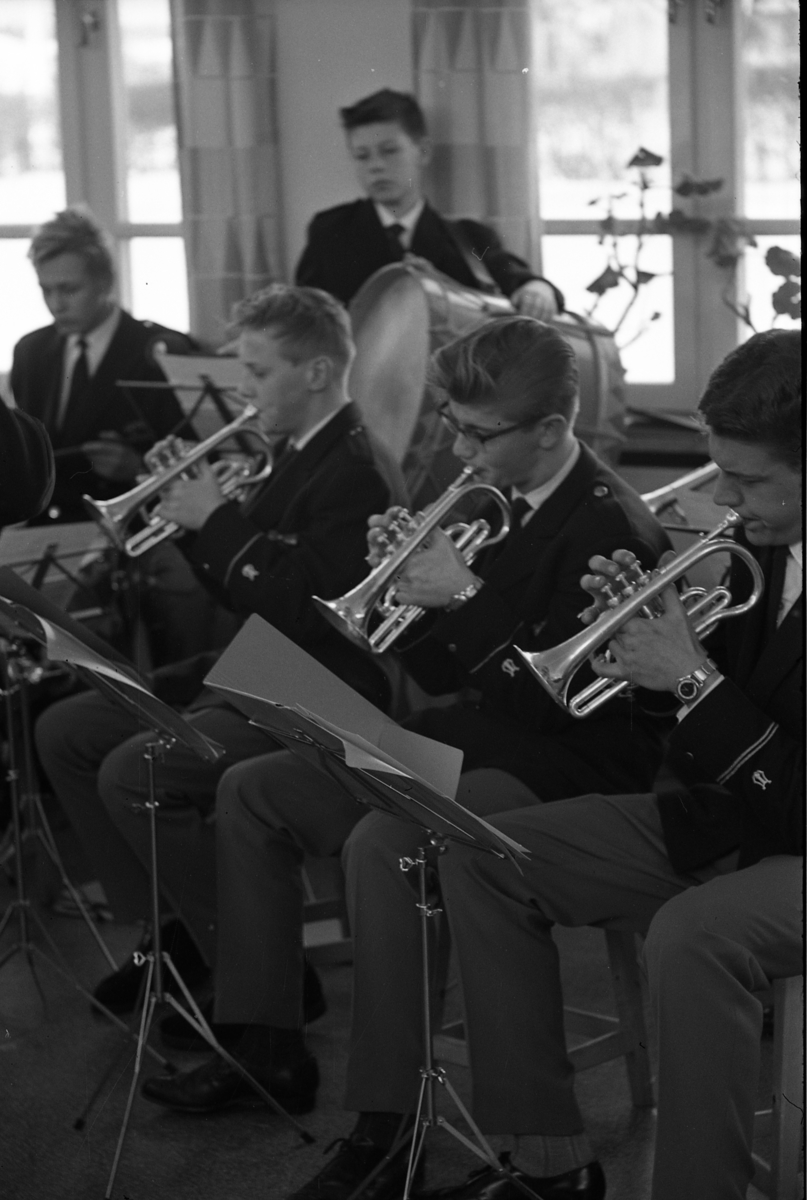 Ungdomsorkestern/Ungdomsblåsorkestern uppträder. Tre grabbar spelar kornett. En slår på stora trumman. Alla är klädda i uniform.