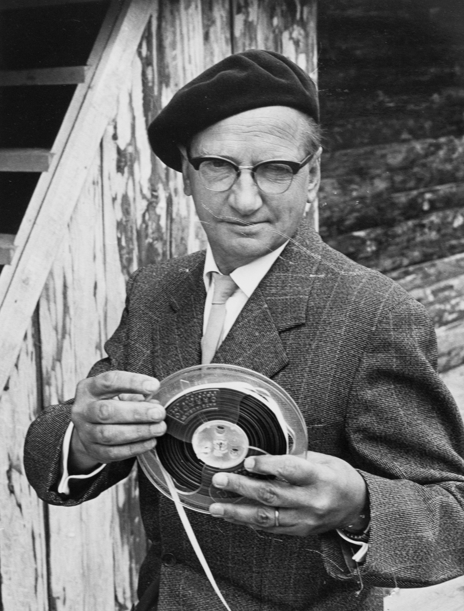 """Elwing Björklund har skrivit musiken till Giv oss fred, eller Arbogaspelet som det också kallas. Man iklädd kavaj och basker. Han håller en filmrulle i händerna. Bilden finns med i Reinhold Carlssons bok """"Arboga objektivt sett"""". Giv oss fred är ett teaterstycke skrivet av Rune Lindström 1961. Handlingen, som är inspirerad av Arbogas klosterhistoria, är förlagt till början av 1500-talet. Uruppförandet skedde den 11 augusti 1962 och Rune Lindström spelade Engelbrekt Gertsson. Lions Club i Arboga stod för arrangemanget. Föreställningarna regnade bort och det blev ett stort ekonomiskt bakslag för föreningen. Spelet har framförts igen; 1987, 1988, 2012 och 2015 av medlemmar i """"Bygdespelets Vänner""""."""