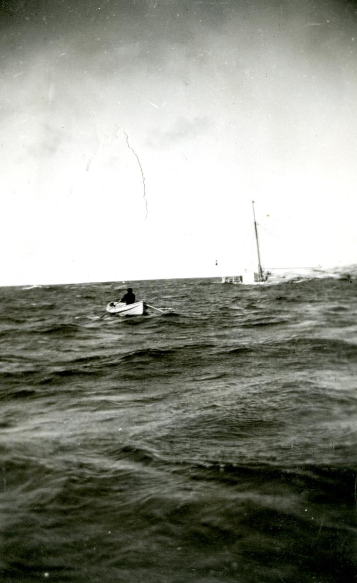 Mann i livbåt og synkende skip. Fra torpederingen av D/S 'Takstaas' i september 1939, fotografert fra torpedobåt KNM 'Storm'