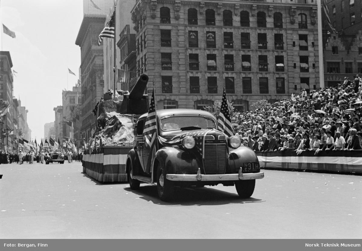Bred bygate med parade bil og tilskuere
