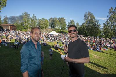 To av kveldens verter; Magnus Sempler Holte og Truls Pedersen, smiler til kamera foran en fullsatt gresslette med gjester.