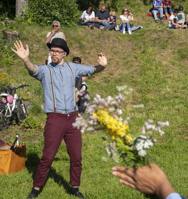 Sjonglør fra Urban Circus, iført røde bukser med bukseseler, skjorte og bowlerhatt, viser sine kunster.