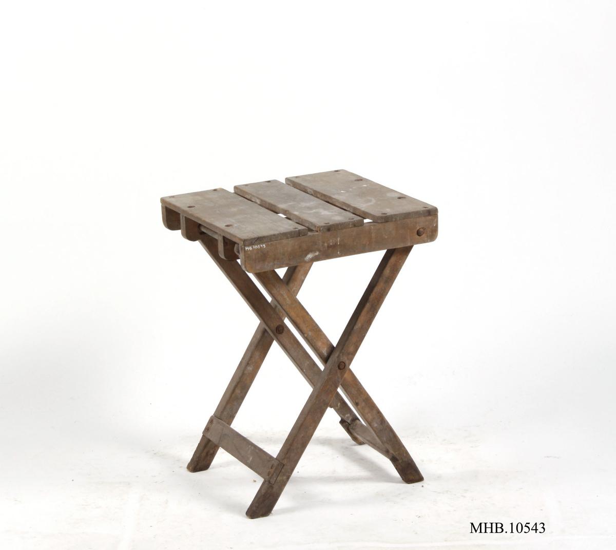 Krakken har fire bein, som henger sammen i par, nederst på hvert par er det en spross som binder de sammen. De er også festet med skruer til en av de motsatte beina omtrent midt på. Det ene settet med bein er skrudd fast til sargen, det andre paret er festet med en pinne mellom hverandre på en skinne, denne mekanismen er skapt for å kunne slå sammen stolen. Det er en sarg som består av to deler på sidene. Setet består av tre planker lagt oppå sargen og skinnen under setet. Setet er kvadratisk.
