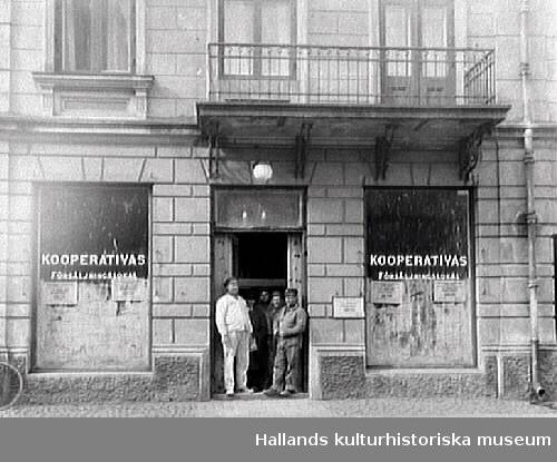 Kooperativas försäljningslokal, vilket förkunnas på båda skyltfönstren. Affären låg utmed Kungsgatan, kv Prosten. Några personer står i dörröppningen. Butiken ligger i ett bostadshus med rusticerad fasad och en balkong utgör även skärmtak över entrén.