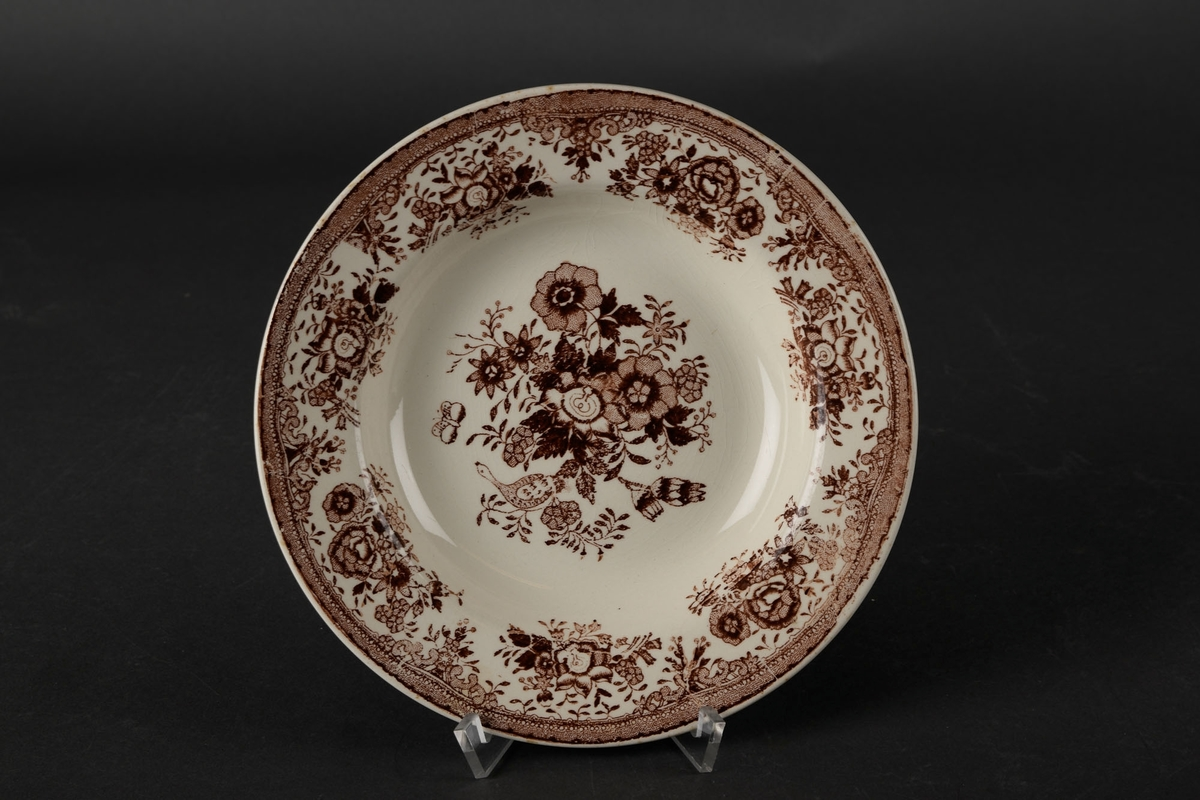 Hvit skål med brun dekor av blomster og fugler.