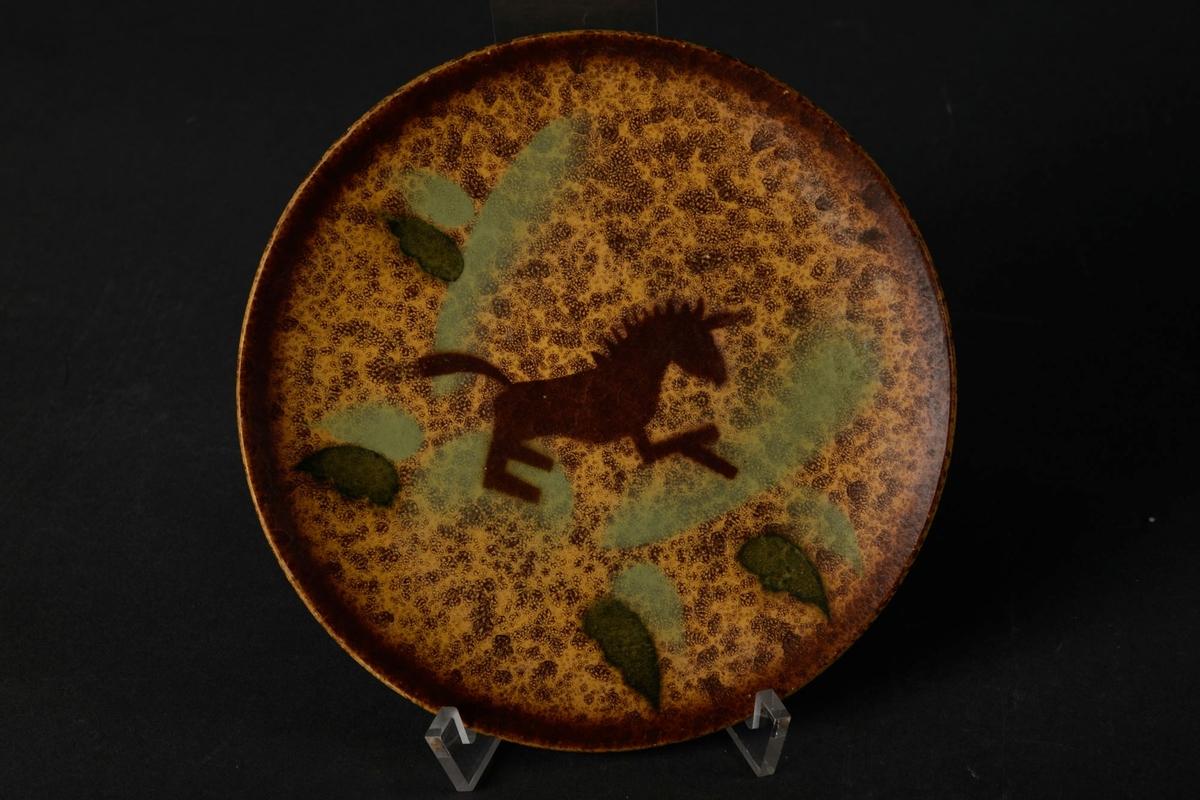 Lysebrunt asjett med mørkebrun dekor av en hest, og grønne blader.