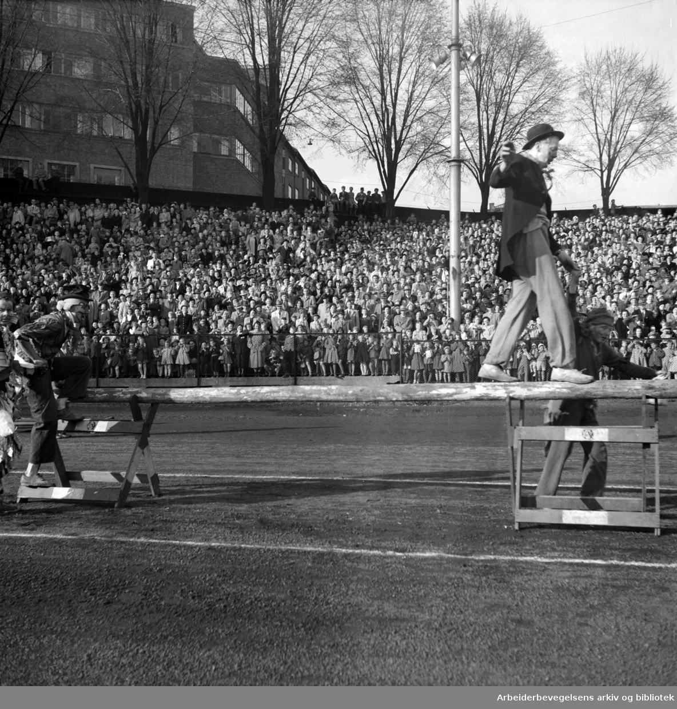 Oslo Framkrets. 1. Mai 1952. Framfylkingens arrangement, Barnas 1. mai på Dælenenga. Grünerløkka Folkets Hus i bakgrunnen. Klovner. Publikum. Tilskuere.