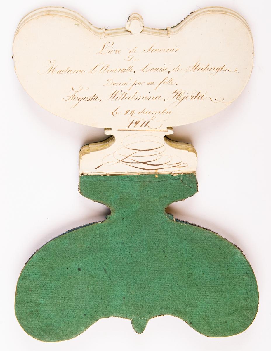 Liten anteckningsbok i form av en urna i empire. Pärmarna klädda i siden, silvertråd och silverpaljetter.  På framsidan: inom hjärta namnet Augusta. På insidan av boken finns namnet Augusta Wilhelmina Hjerta som sannolikt fått boken i julklapp 1811.