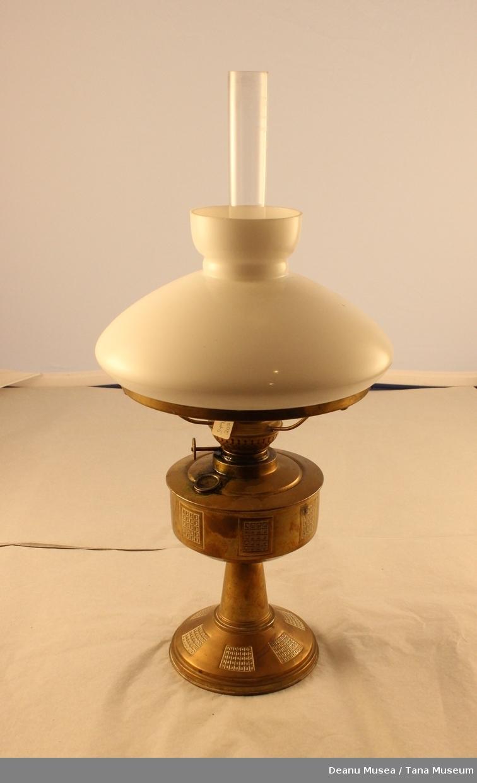 Parafinlampe  i messing som innholder lampeolje. Lampeskjerm i hvit glass. lampeglass i klar glass.