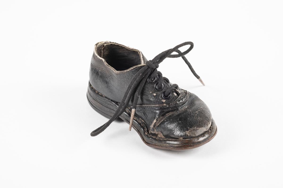 Et randsydd barnesko (venstre sko) av lær. Skoen har snøring med runde lisser. Maljene er av metall. Sålen er av lær og er forsterket med spiker på hælen og ved tuppen på undersiden.