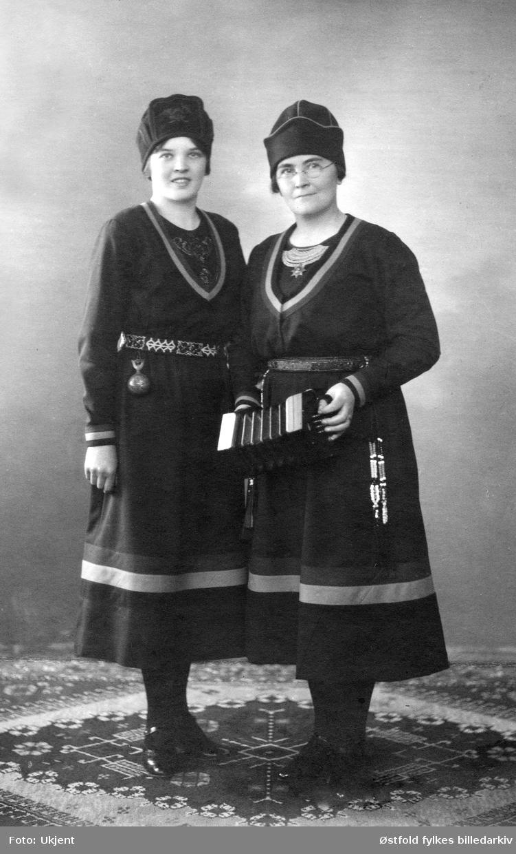"""Studioportrett av Ziga Wickström og Anna Lisa Öst, også kalt Lapp-Lisa, til høyre. I sin tid var Lapp-Lisa  en av Sveriges mestselgende plateartister med sanger som """"Barnatro"""", """"Drinkarflickans död"""" og andre.   """"Kvinnan till vänster om Lapp-Lisa är hennes brorsdotter Ziga Wikström, född 1910 i byn Mark, Vilhelmina socken, Sverige. Ziga kom 1926 som hembiträde till sin faster Lapp-Lisas familj i Hedemora, Dalarna. Snart började Ziga sjunga och resa med sin faster. Bland annat reste de sju månader i Norge. Ziga utbildade sig sedan till officer i Frälsningsarmén. Tillsammans med maken Sigvard blev Ziga evangelist i pingströrelsen. Ziga var otroligt stor som grammofonartist och det finns skivor där Einar Ekberg sjunger på ena sidan och Ziga på den andra.  Släktforskning har visat att det visst finns samiskt påbrå hos dessa sångerskor från Lappland. En anfader kallades för Grårocken."""" """"Dessa sameättade nybyggardöttrar från Vilhelmina reste sju månader i Norge 1930. Bilden här användes troligen som PR-bild under den sångarresan. Fotografen var verksam i Hedemora, Dalarna, där Lapp-Lisa också var bosatt. Konsertinan var lätt att ha med sig på resor, då den inte vägde så mycket som t ex ett dragspel. Därför kom instrumentet att användas av Frälsningsarmén. Båda dessa sångerskor var knutna till Frälsningsarmén. Ziga gick dock senare över till Pingströrelsen. Under många år var Lapp-Lisa den mest önskade artisten i norska Önskekonserten, med sången Barnatro."""" (Marcus Brännström 2021)  Samisk drakt (sørsamisk?), kofte /gapta og lue men skoene hører ikke til drakta.  Instrumentet er en concertina med English System. Concertina var et instrument som gjerne ble brukt av sjømenn (lett å ta med seg). Det ble  utviklet i England 1829 (Sir Charles Weatstone), opprinnelig med tanke på at det kunne bli et konsertinstrument. Men det gikk fort over til å bli et folkemusikkinstrument."""
