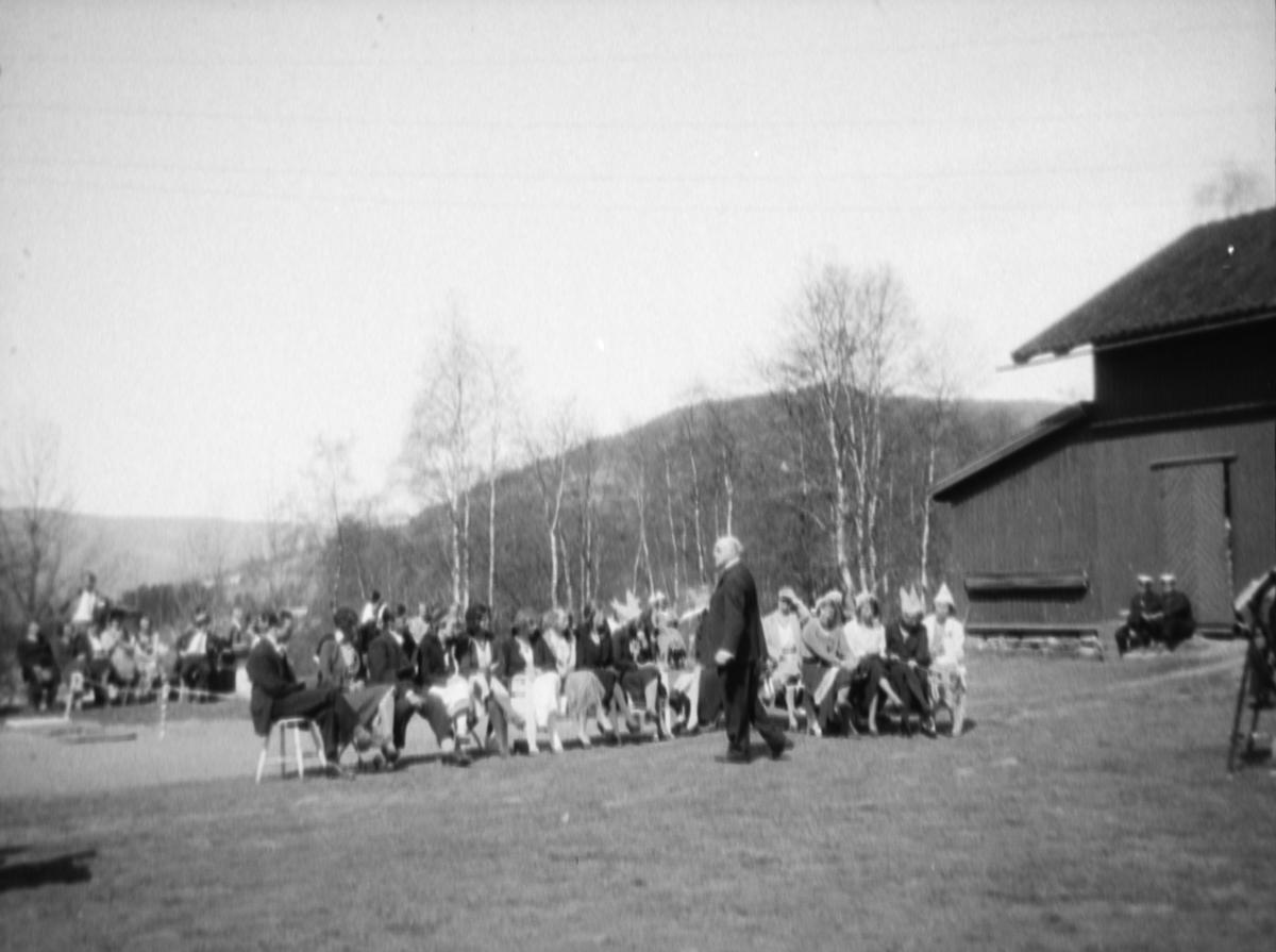 Samling av mennesker som sitter på stoler utenfor Kornhaug, Follebu.