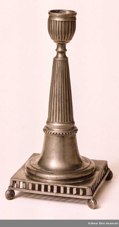 KLM 5651. Ljusstake av tenn. Foten fyrsidig med genombrutna smala sidstycken vilande på fyra rundade små fötter. Skaftet runt, avsmalnande uppåt, räfflat. Ljushållaren räfflad. Hattens rand trubbtandad (skadad). Årsstämpel G3 (1813), 2 mästarstämplar: JPF (Johan Petter Fagerström, 1798-1837), 2 stadsstämplar, 1 kontrollstämpel. En i ett par, hör samman med KLM 5650.
