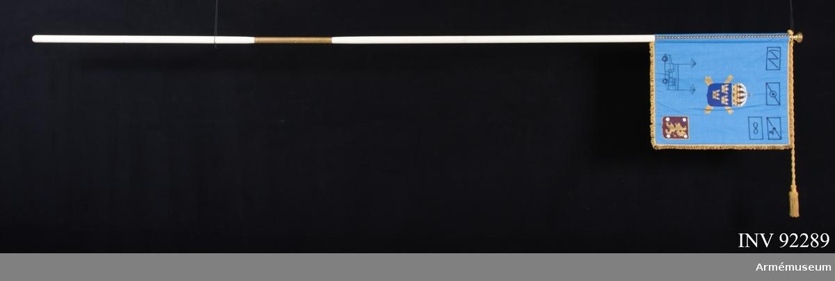 Dubbel duk kantad med frans. Dekoren målad på duken. Spetsen är en gardinknopp i metall. På duken syns Svea artilleriregementes vapen i mitten och Östergötlands landskapsvapen i nedre yttre hörnet. I överkant syns fyra plutonstecken för: radar, ljudmätning, jägare, helikopter. Bilen symboliserar staben.