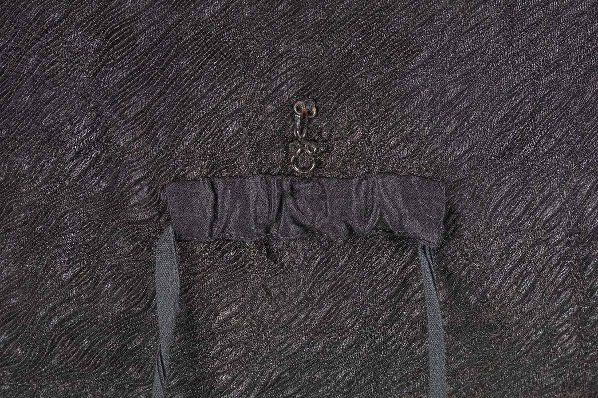 Svart kjoleliv av chiffon (?) med foring av bomull. Den har puffermer og høy hals. Halsen og mansjettene er sydd i folder. På baksiden er det påsydd et snor trolig for snøring. Over snoren er det en hemp og hekte i metall. Kjolelivet lukkes med metallhekter. Det er brodert bokstav T på innsiden av kragen.