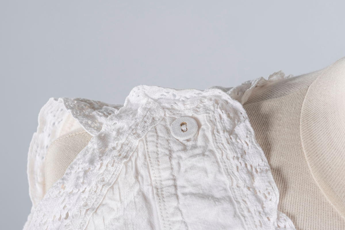 Linnet uten ermer og med knepping i skuldrene. Det er heklet blonde i halsåpningen og i ermeåpningene.