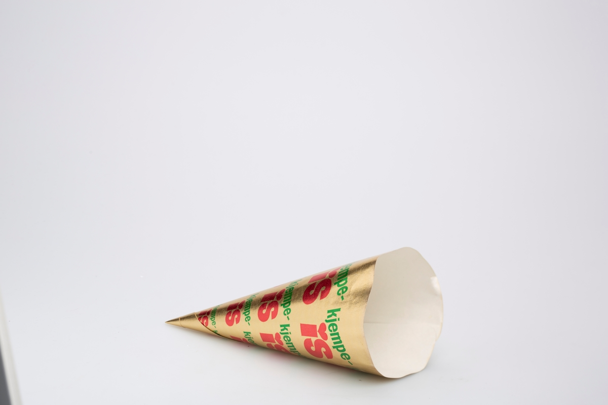 Kjegleformet iskrempapir (kremmerhus) i aluminium og papir. Kremmerhuset er med farger på utsiden, og uten farge (hvit) på innsiden. Den har gull bakgrunnsfarge med varenavnet spredt rundt på hele papiret.