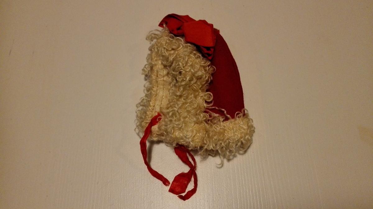 Lita kyse av ullstoff kanta med flausch-liknande stoff. Fora med skinkelerret. Silkeband under haka. Sløyfe av raude ripsband på toppen.
