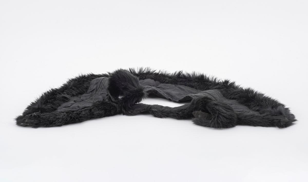 Delen som skal vende ut er i svart silke. Delen som vender inn i svart ull. Vattering med stikninger i linje-/rutemønster. Selve vatteringen ser ut til å være i noe blandingsstoff av ull og annet organisk materiale. En svart pelskant går langs nedre kant og opp langs spissene i hver ende av kragen. Fra ende til ende på kragen går pelskanten slik at den etter all sannsynlighet har omsluttet en lue eller hette som har vært festet til kragen i nakkepartiet. Denne luen/hetten er sannsynligvis GH.03314.  Denne er i samme stoff og utførelse, og passer dersom vi legger de to delene sammen.