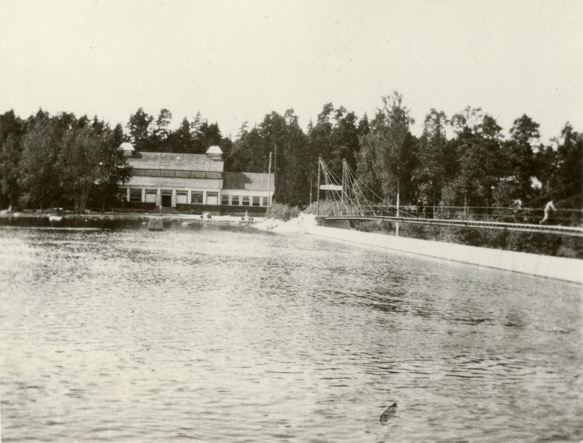 Byggnad och bro vid vattendrag.