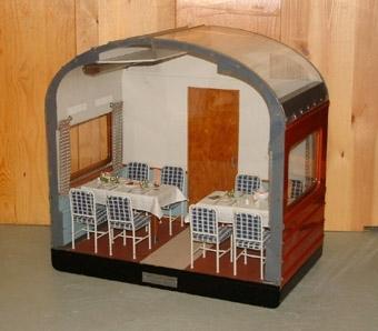 Modell i skala 1:5 av en sektion av en RO 3 restaurangvagn. Inredningen har brun och beige golvbeläggning, samt grå väggar och tak.  Brun dörr, och brunvita randiga gardiner.  2 bord dukade för måltid, med 8 stolar med sits och ryggstöd klädda med blått och vitt rutigt tyg.