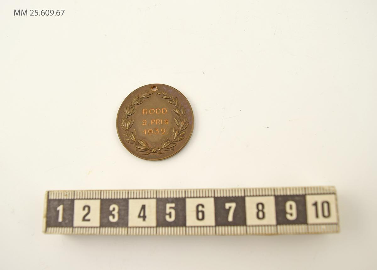 Mynt i brons. På framsidan Kustflottans emblem med ankare och tre kronor som flankeras av två örlogsflaggor. På baksidan text som omges av lagerkrans.