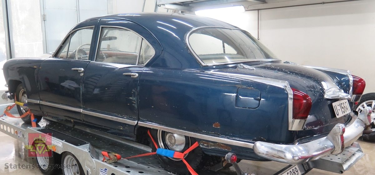 Blå 4-dørs bil med grått, blått og brunt interiør. Bakhjulstrekk. 6-sylindret bensindrevet motor.