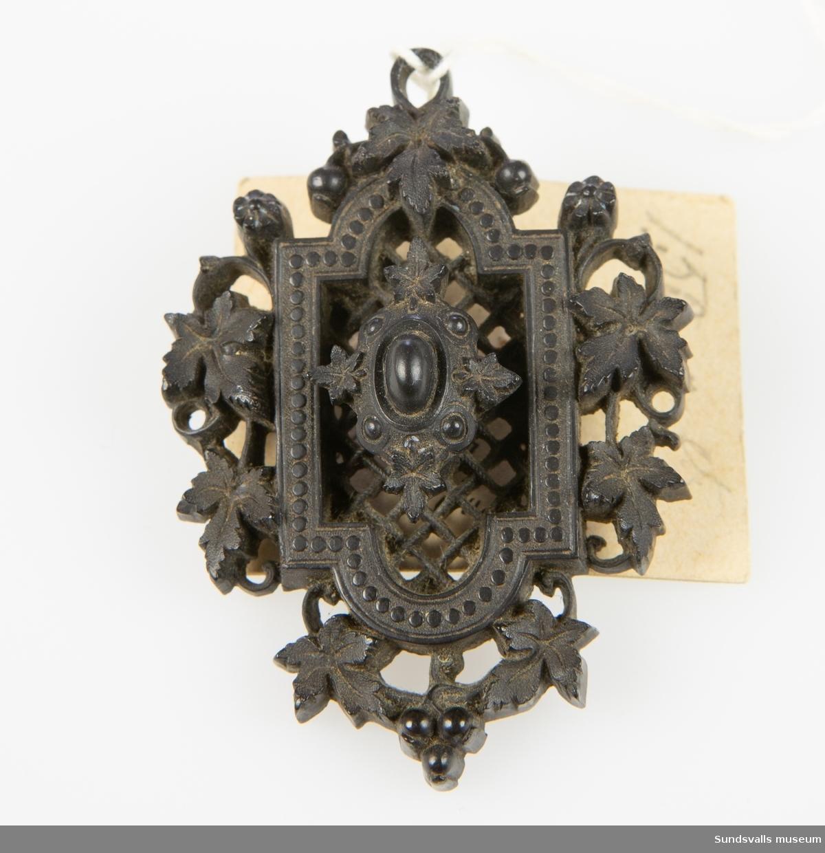 Brosch av svart material med skuren eller gjuten ornamentik föreställande bl.a. vinblad och blommor. Metallnål på baksidan.