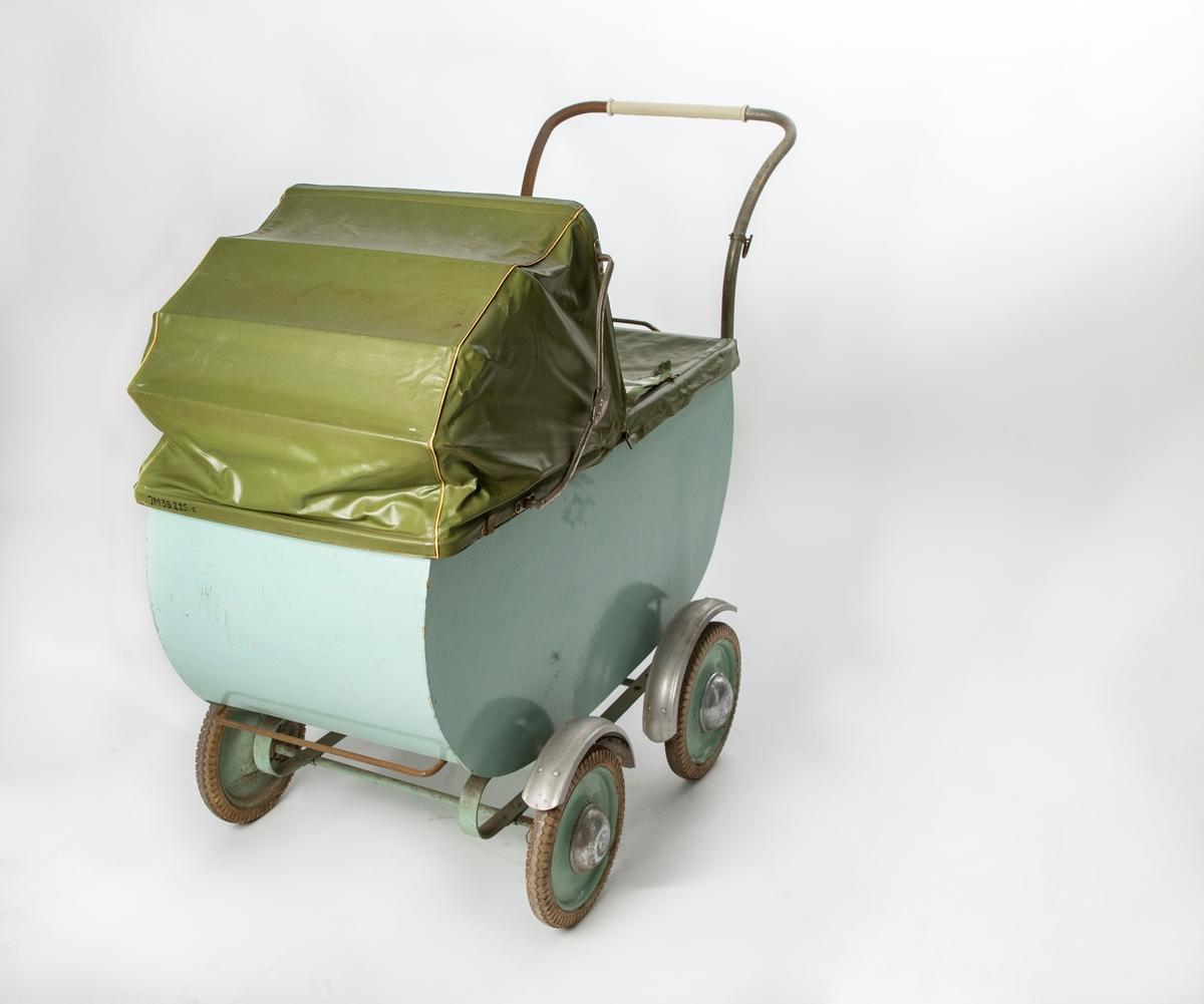 """Ljusgrön barnvagn av trä med rundade nederkanter, delvis rostigt handtag, vit plast i framkanten. Firmamärke: """"F Ö (däremellan en figur), svensk tillverkning"""". Grönmålade gummihjul med stänkskärmar av plåt. Till vagnen hör även sufflett JM 35.225:2, löstagbart av grön nylon, och vindskydd JM 35.225:3 av grön galon med fönsterruta av genomskinlig plast."""