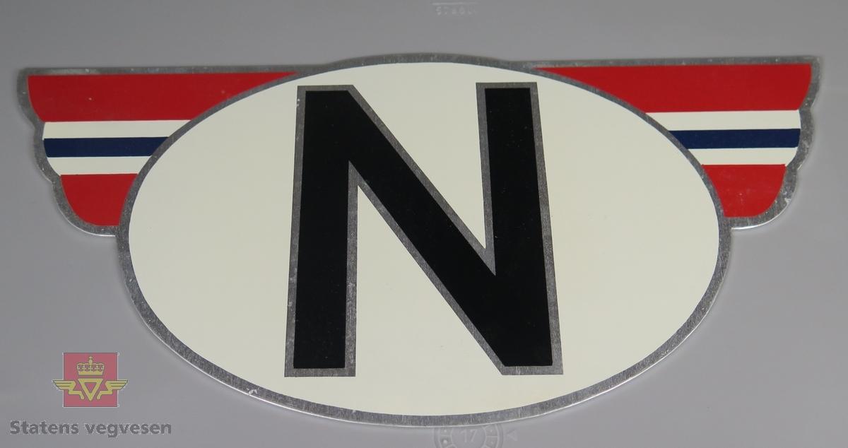 Skilt av aluminium. Bokstaven N i svart på hvit bunn omkranset av vinger i rødt, hvitt og blått. Emballasje med informasjon fra produsenten.