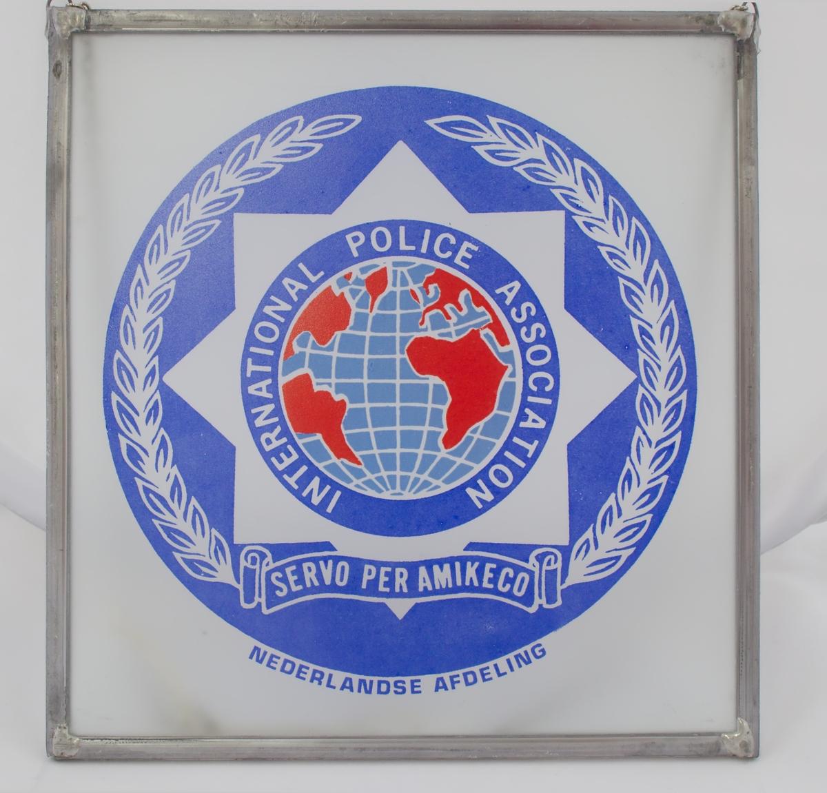 Glassbilde med IPAs logo med stålramme og sølvfarget lenke.