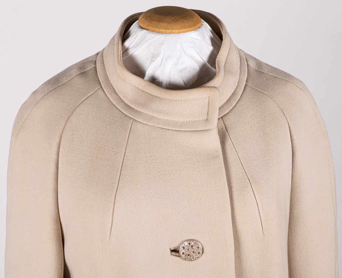 Vit yllekappa av A-modell från 1960-talet. Tillverkad av Tissu Francais Normant, Paris. Stående krage och knäppning med två knappar framtill.