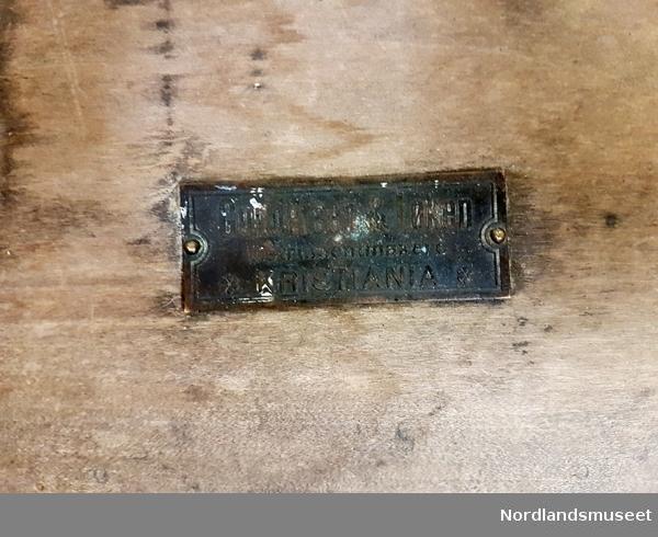 Nivellerkikkerter med fot og 3 justeringsskruer og skrin i lakkert eik. Kikkerten er påmontert rørlibelle på toppen. Kikkerten er montert på feste med festeskruer i messing for montering på stativ. Serienummer 394 er preget inn i kikkerten. I skrinet er det montert fire filtbelagte klosser formet for å passe instrumentet og sikre transport. Kassen har klipslås med spenne i metall og låsbeslag. Selve låsen er fjernet, og det er hull på innsiden bak låsbeslaget. På lokket er festet et metallskilt fra produsenten Gundersen & Løken, Instrumentmakere, Kristiania. Visittkort i papir montert på innside av lokket. Skrinet er sprukket i bunn. Bærereim i lær.