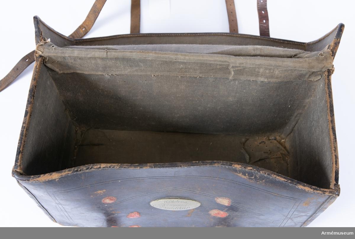 """Läderväska för expeditionsmateriel hörande till Vadstena kompani vid Andra Livgrenadjärregementet. Väskan är dekorerad med inskurna lister runt kanterna samt romber innanför. På undersidan finns 5 metallfötter. På lockets vänstra kant finns rester av transportetiketter där orten Ödeshög syns. Märkt på metallskylt på framsidan """"Wadstena Kompani Expedition"""". Runt skylten finns rester av 7 lacksigill. På baksidan finns 4 lacksigill. Väskan är troligen från andra hälften av 1800-talet. Den ska fungera som ett portabelt kontor och ska innehålla stämplar, blanketter, skrivmateriel mm. Väskan är tom."""