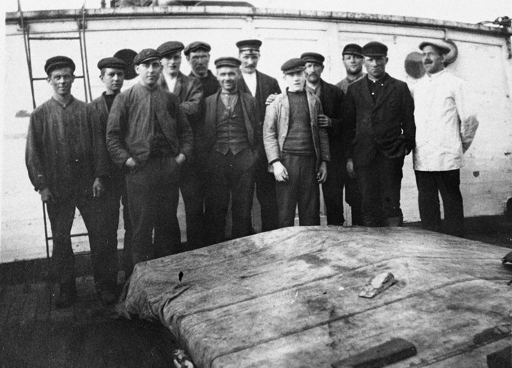 """Mannskapet på """"Minærva"""" i Barentshavet i 1919. Kristoffer Sandved også kalla """"Trappen"""" tok biletet. Han var og eigar av båten.  Nr. 1 frå venstre er Ommund Tunheim, 15 år og fyrbøtar. Til høgre står Karl Johan Tunheim Greiestad som var kokk og vart kalla """"Greiesten"""". Sjå også 1990.1TIM.28.014"""