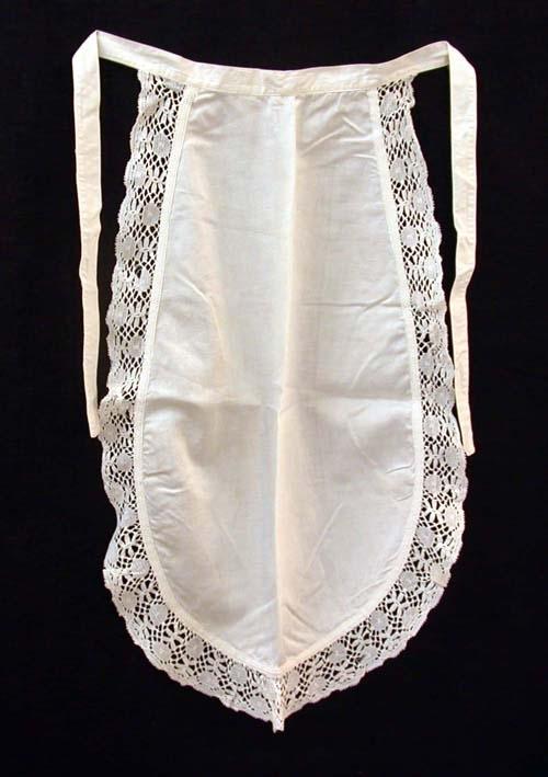 Ovalt serveringsförkläde i vitt, satinvävt bomullstyg, kantad med ca 50 mm bred spets. Cirka 20 mm bred linning som går i ett med knytbanden.