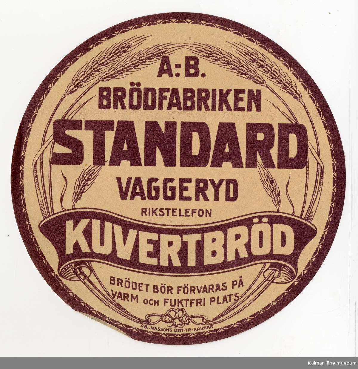 KLM 21360:3:28 Etikett, av papper, tryck av litografisk etikett. På etiketten text: Standard Kuvertbröd. I färgen brun text på beige bakgrund. Etikett till knäckebrödsförpackning. Beställare: A.-B. Brödfabriken, Vaggeryd. Tryckt på Janssons Litografisk tryckeri i Kalmar. Trycket låg löst i provbok med varuetiketter mm, KLM 21360:1.