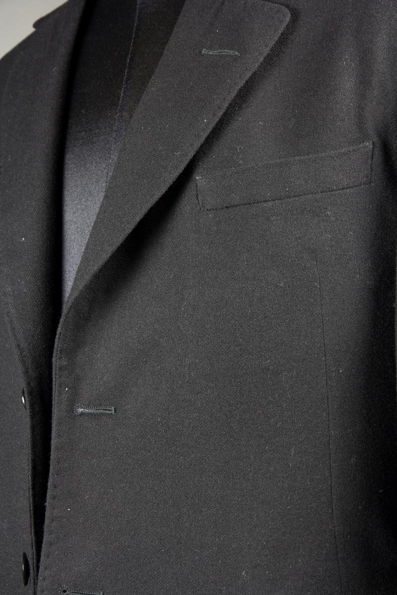 Kavaj till tredelad svart yllekostym. Stängs med två knappar. Har en bröstficka och två fickor med lock. En innerficka. Blå- och vit-randigt foder av bomullssatin i ärmarna. Svart foder i övrigt. Plagget är sytt med klassiska skrädderimetoder som innebär underarbete och handsömnad.  Kavajen är uppbyggd med löst vattulin pikerat med bröstvattulin. Bröstfickan är en stolpficka med löst belägg prickstickad i överkant. Krage är dubblerad och pikerad med kläde och kraglärft. Dubbelpasspoalerade sidfickor med prickstickade lock. Kläde och tyg på kragen är stosade. Kanter är prickstickade längs slag och krage. Kavajen har ingen axelvadd, men ett lager shetlandsull, samt shetlandsull i regling, vaddvingar i kakvadd/vattulin. Handstofferat foder. Ärmslits utan sydda knapphål, knappar är isydda rakt igenom för att stänga ärmslitsen utan knapphål. 2st handsydda knapphål i polyestertråd fram utan iläggstråd, samt slagknapphål med iläggstråd på kragens slag.