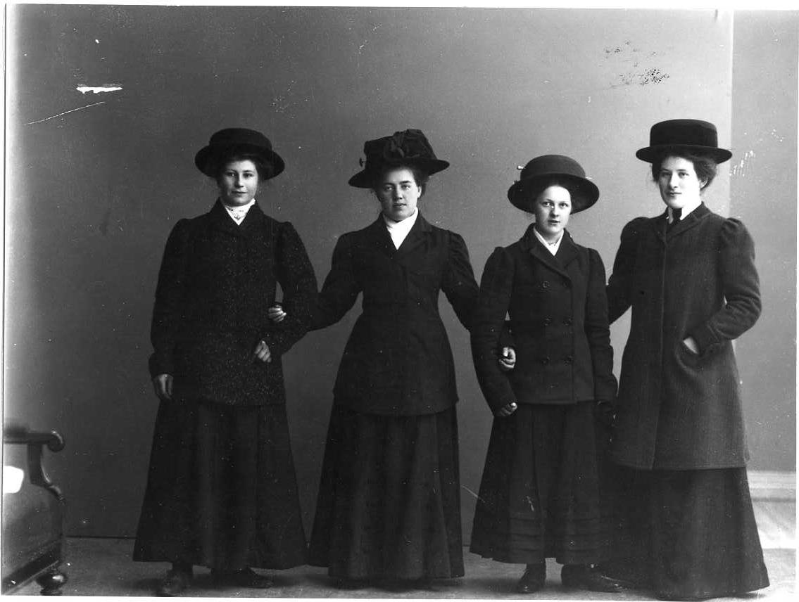 Gruppbild med fyra unga kvinnor i ytterkläder och hatt på huvudet. Från vänster: Elvira Pettersson från Bohult, Edla Andersson från Aranäs, Elsa Tell samt Hanna Blixt från Aranäs.